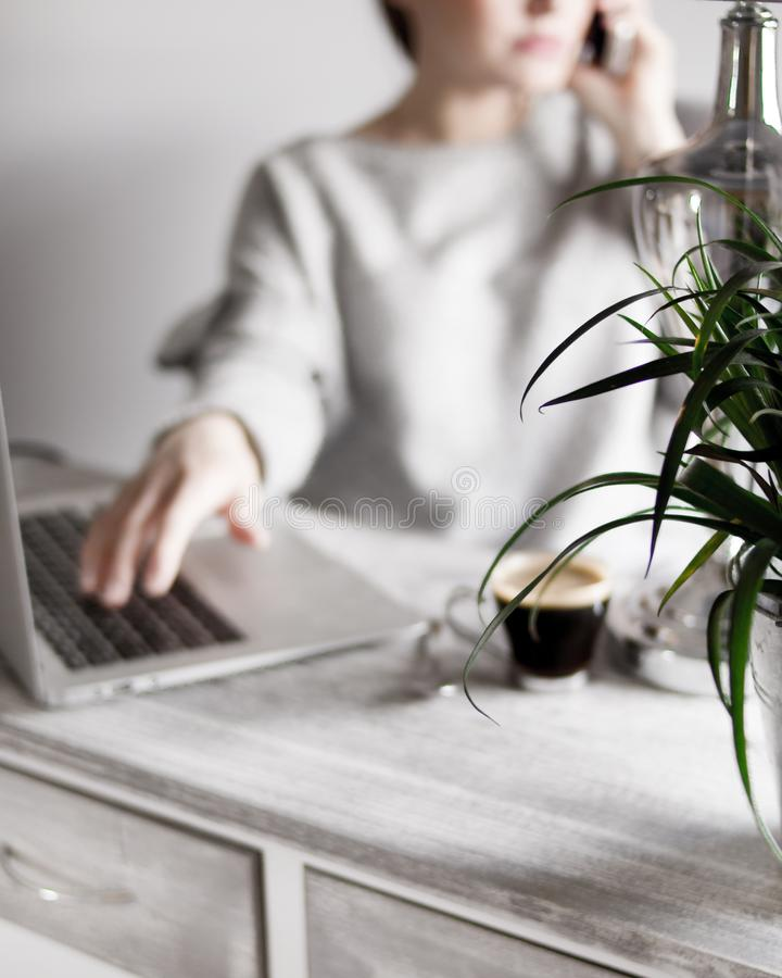 Femmina in un maglione grigio che parla sul telefono con la sua mano su un computer portatile e su un caffè sulla tavola immagini stock