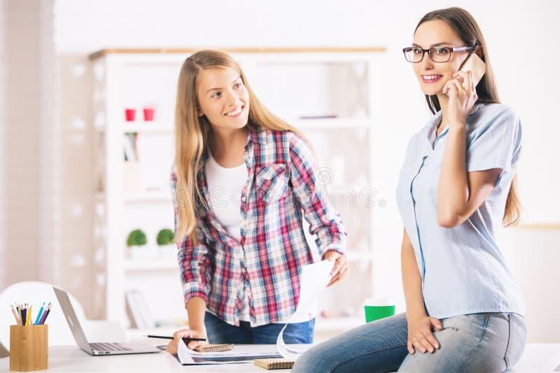 Femmine che lavorano e che parlano sul telefono immagine stock