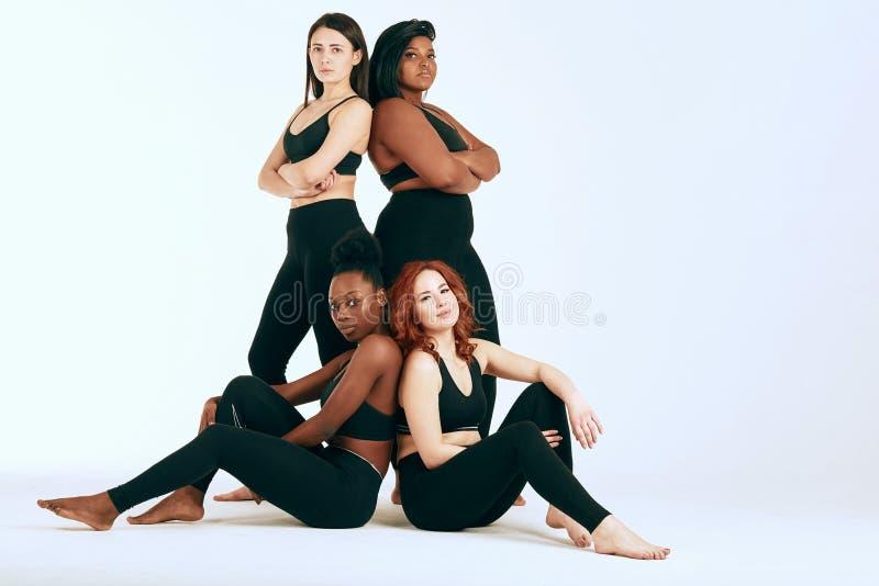 Femmine multirazziali con il supporto differente di etnia e di dimensione insieme ed il sorriso immagini stock