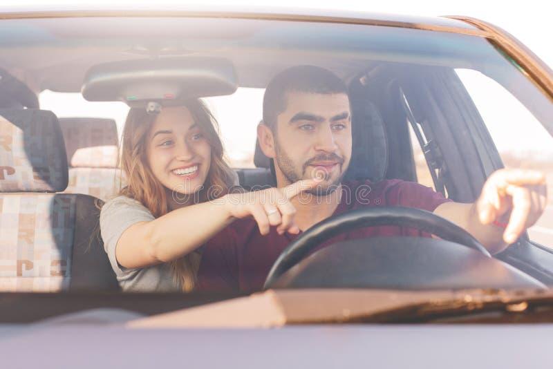 Femminili e maschii emozionanti in automobile, punti al tergicristallo, avviso qualche cosa di divertente sulla strada, godono de immagine stock