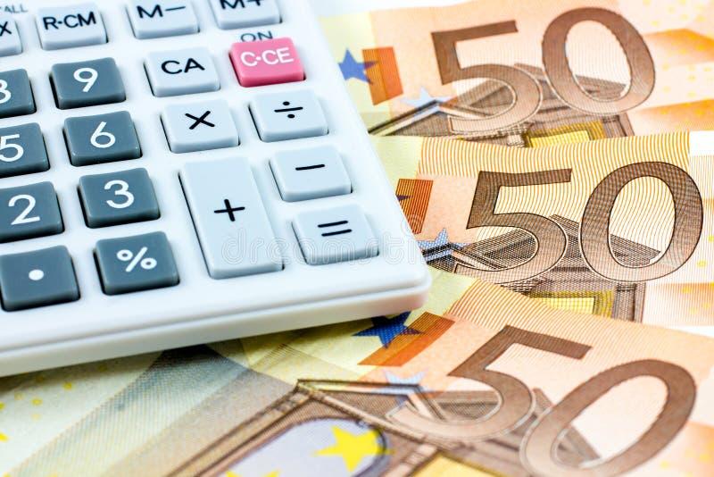 Femtio euroräkningar och en räknemaskin royaltyfri foto