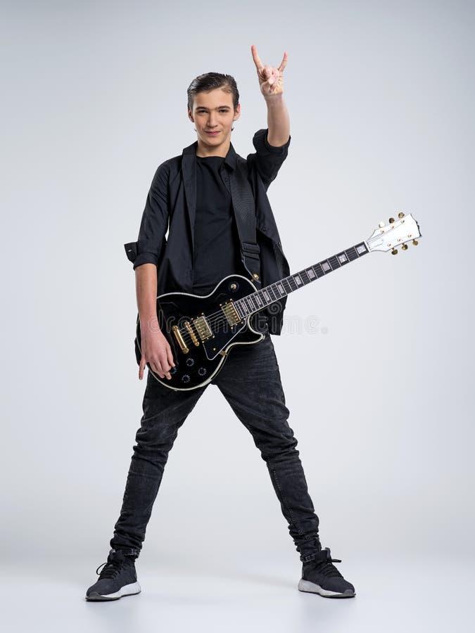 Femton år gammal gitarrist med en svart elektrisk gitarr Den tonårs- musikern rymmer gitarren royaltyfria bilder