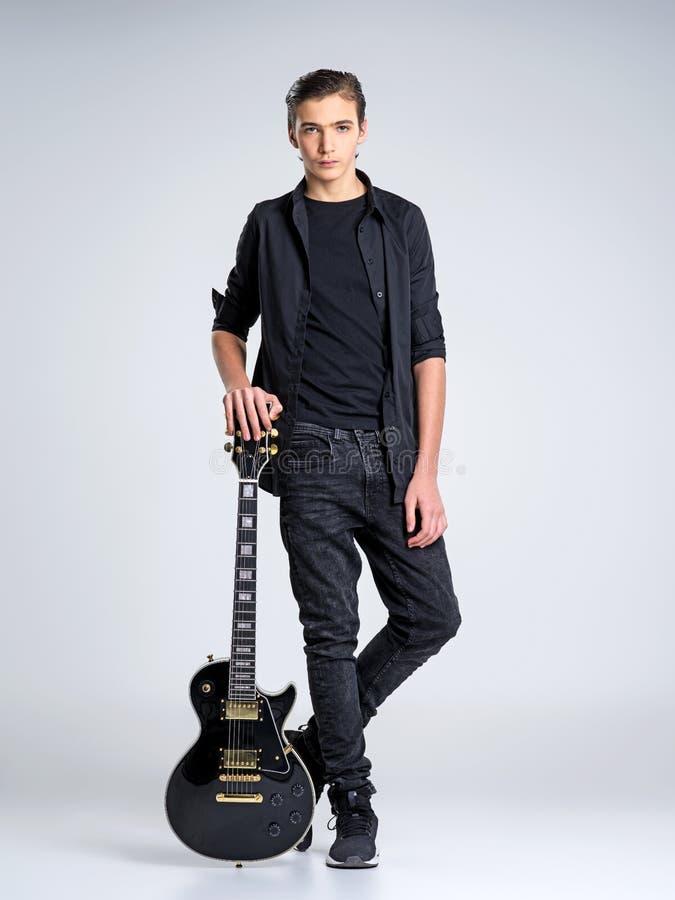 Femton år gammal gitarrist med en svart elektrisk gitarr arkivfoton