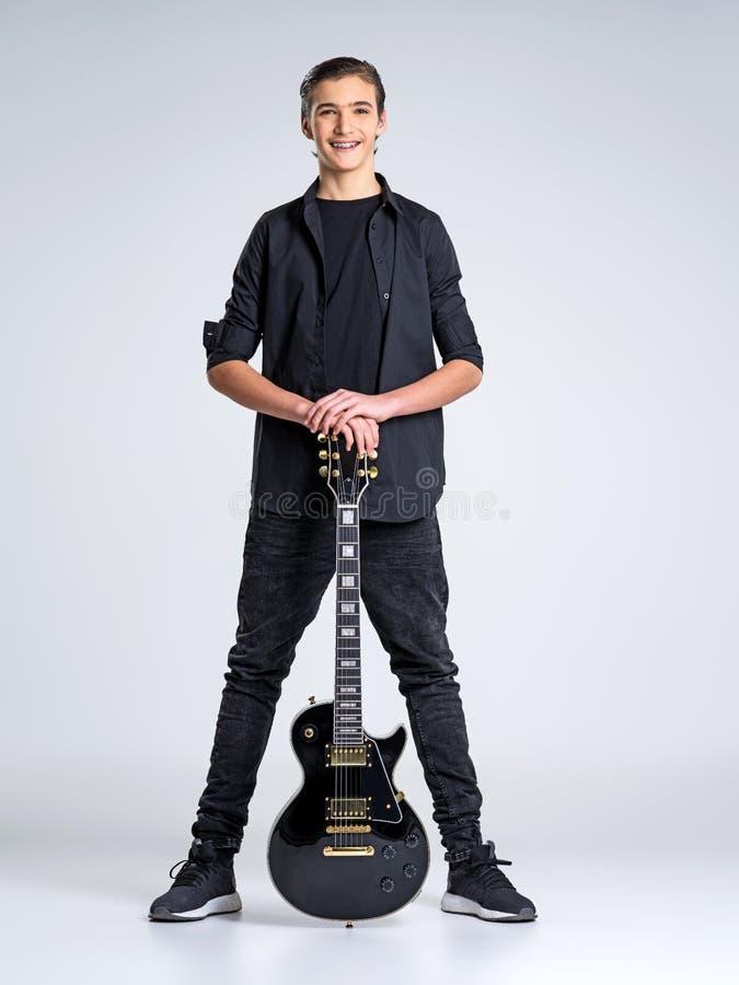 Femton år gammal gitarrist med en svart elektrisk gitarr arkivbilder