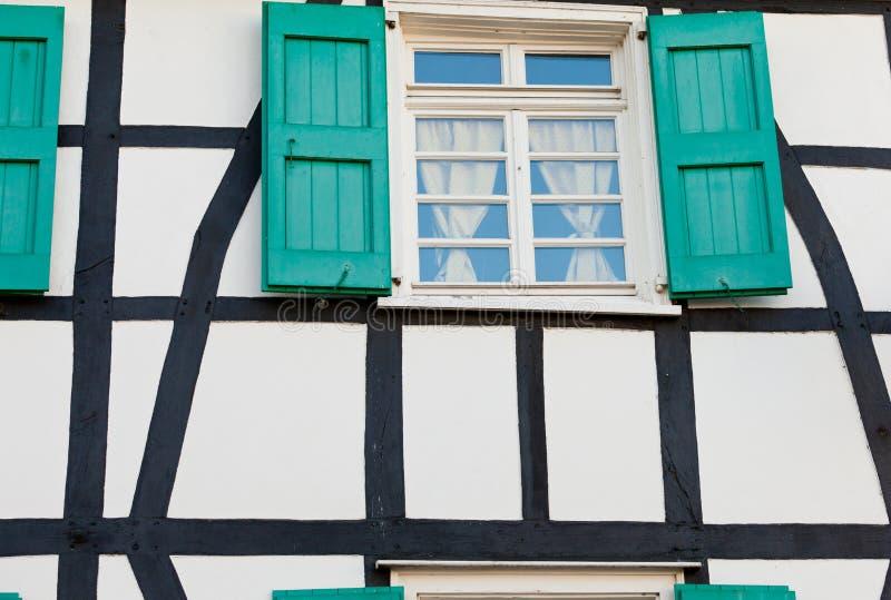 Fenêtre à volets dans une maison de structure de bois allemande photos libres de droits