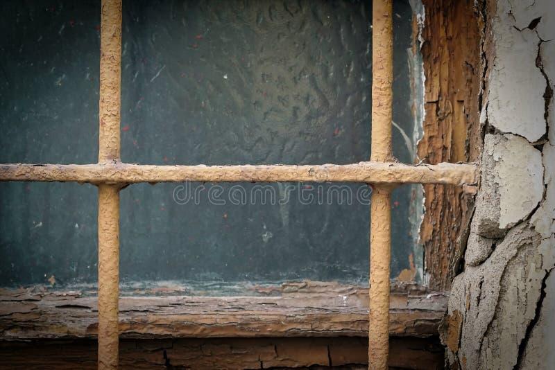 Fenêtre avec des barres de fenêtre sur une maison de diminution des effectifs image stock