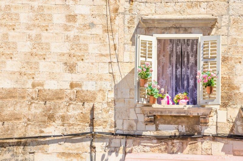 Fenêtre avec des fleurs sur le fond d'un mur en pierre blanc typique de l'architecture en Croatie photographie stock libre de droits