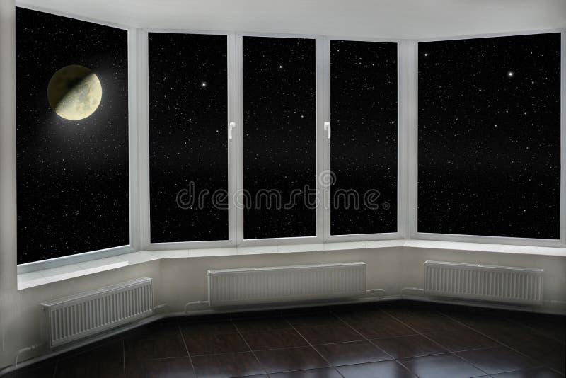 Fenêtre avec la vue à musarder et le ciel nocturne foncé Étoiles et lune image libre de droits