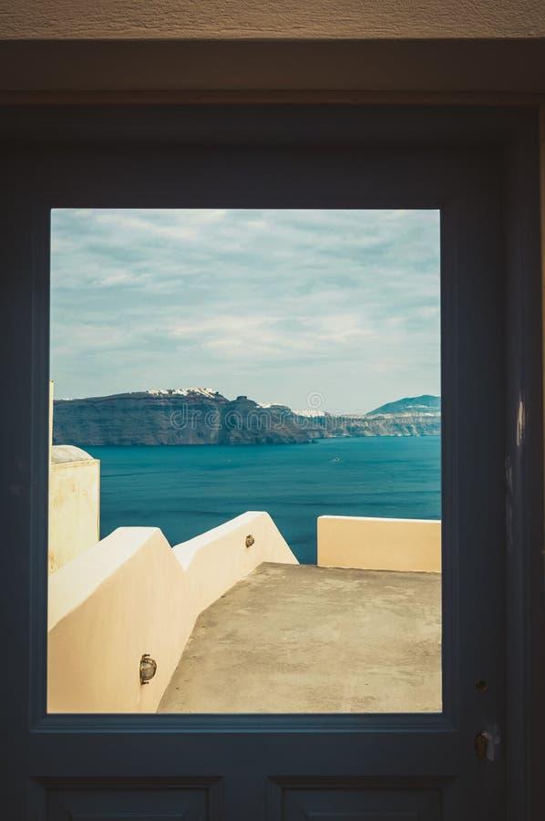 Fenêtre avec la vue de Thira et la caldeira du volcan de Santorini photo stock