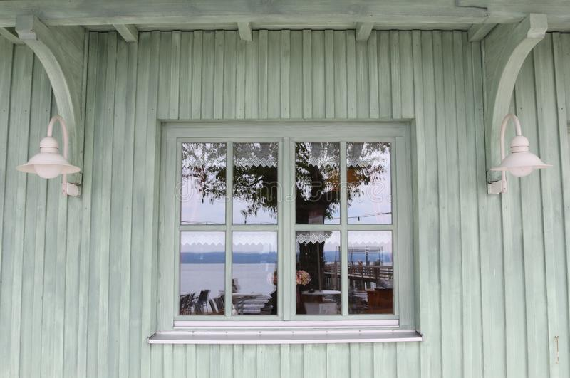 Fenêtre blanche de cru dans un mur en bois peint vert blanc de maison avec des réflexions des articles environnants image libre de droits