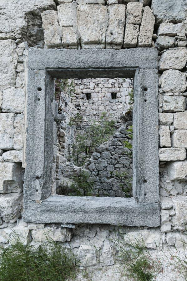 Fenêtre carrée dans un mur pierreux de vieilles ruines en Slovénie images libres de droits