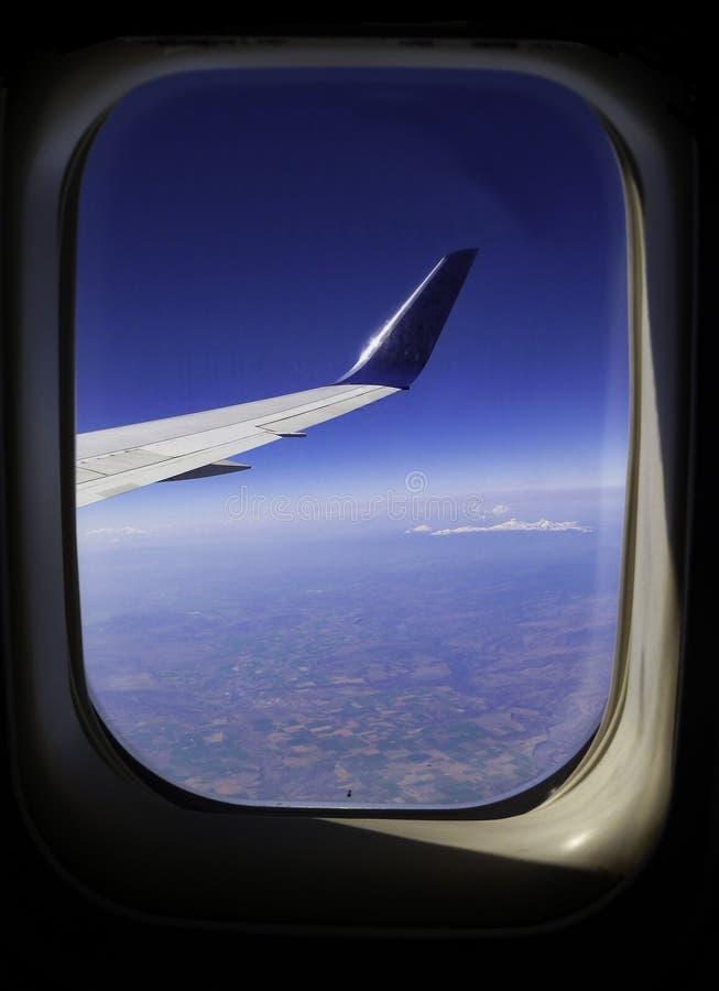 Fenêtre d'avion regardant l'aile, le ciel, et le bel au sol image stock