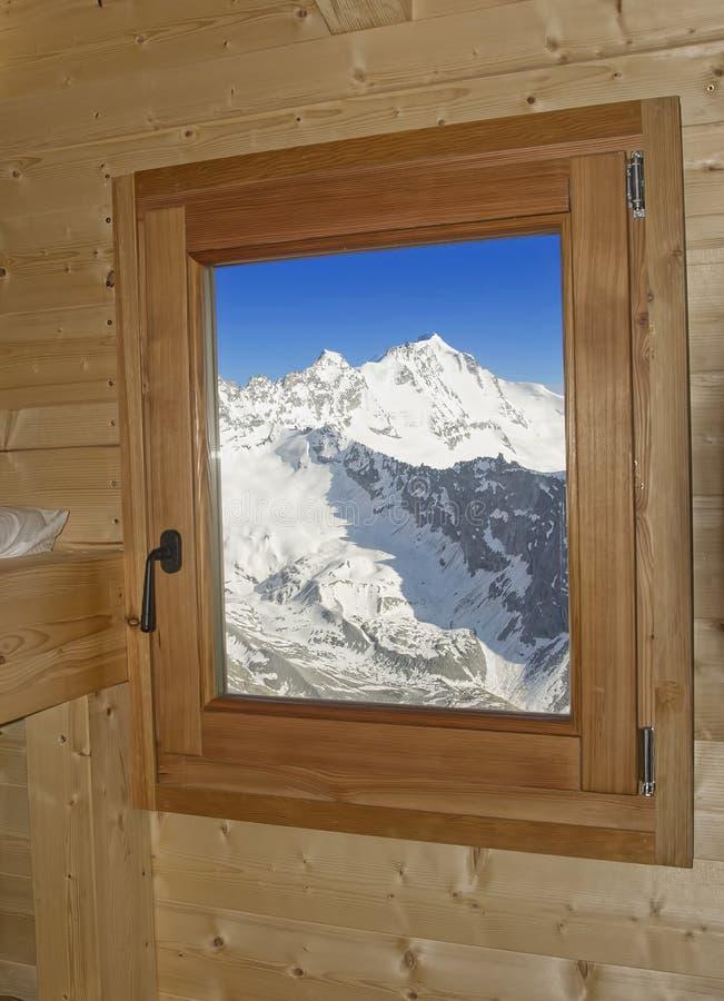 Fenêtre dans la hutte en bois avec le paysage alpin de montagne photo stock