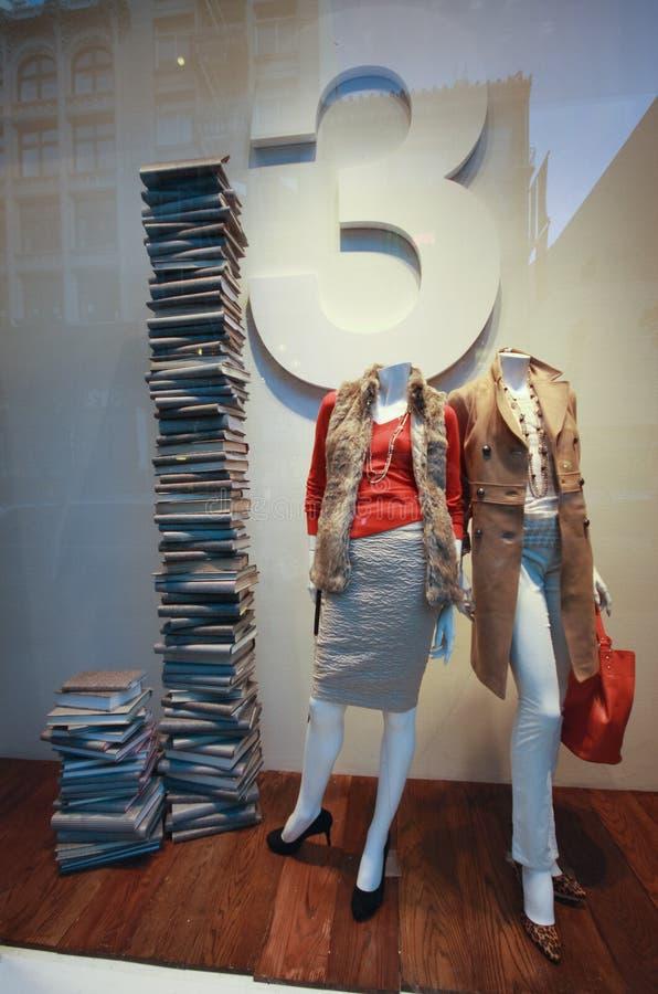 Fenêtre de boutique de boutique avec les mannequins habillés et la haute pile de la BO photo stock