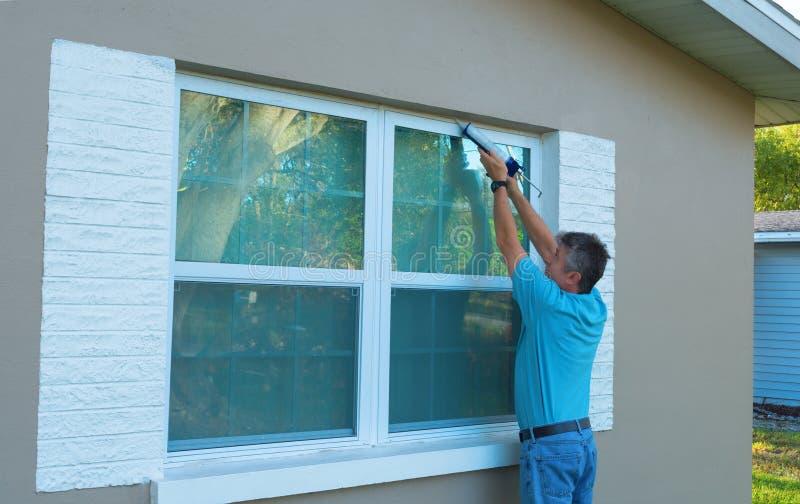 Fenêtre de calfeutrage de propriétaire d'une maison protégeant contre les intempéries à la maison contre la pluie et les tempêtes photos libres de droits