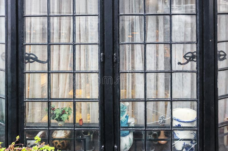 Fenêtre de maison intime modeste - fenêtre en saillie noire cassée en métal avec les rideaux nets et les bibelots se reposant à l photos stock