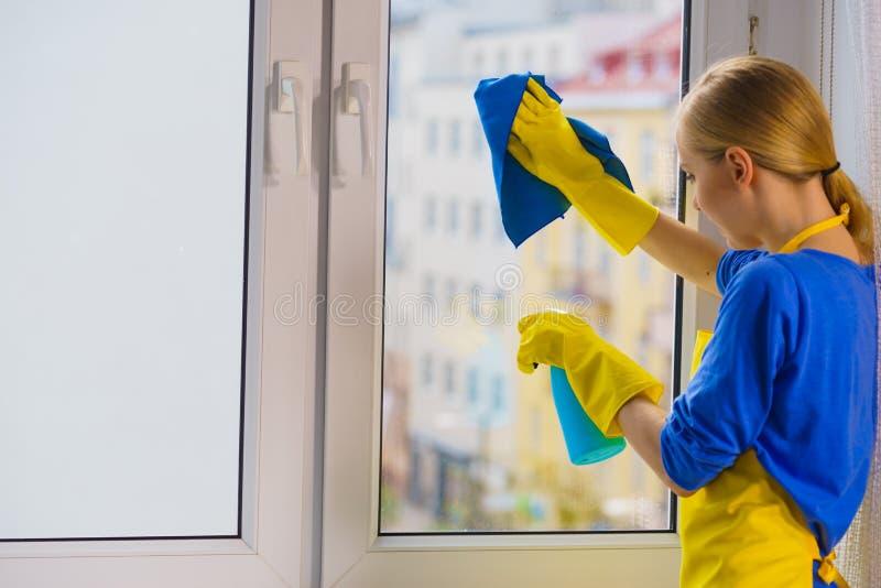 Fenêtre de nettoyage de femme à la maison photos libres de droits