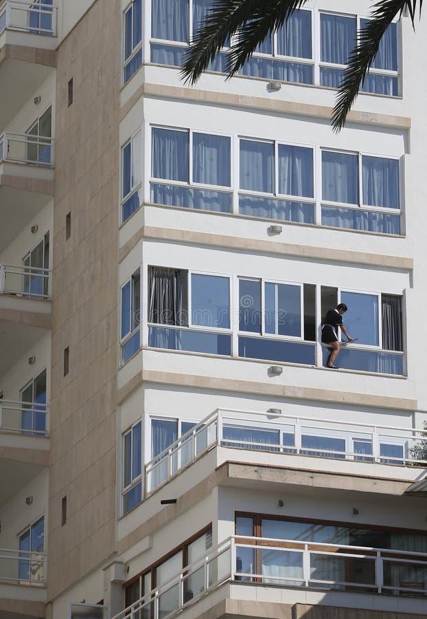 Fenêtre de nettoyage de femme de chambre sur une façade d'hôtel dans la verticale de Majorque photographie stock