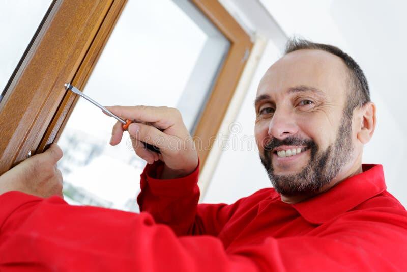 Fenêtre de sourire de fixation d'homme utilisant le tournevis photo libre de droits