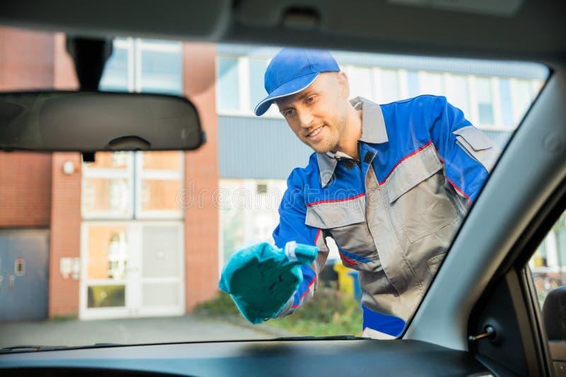 Fenêtre de voiture de nettoyage d'homme avec le tissu photos stock