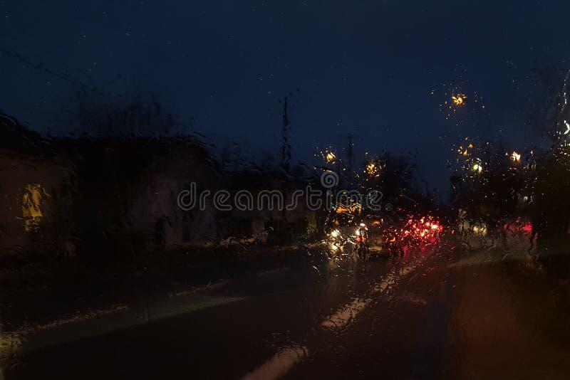 Fenêtre de voiture humide avec le fond de la chute de pluie de circulation urbaine de nuit la nuit avec les voitures troubles photos libres de droits