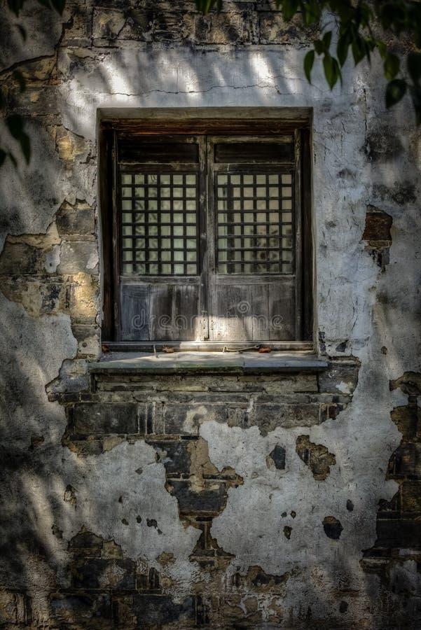 Fenêtre en bois dans une maison de mur en pierre avec le plâtre couvrant certaines des briques à Suzhou Chine photo libre de droits