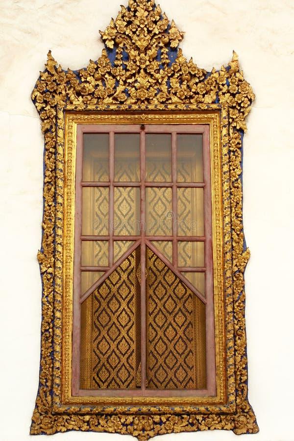 Fenêtre en bois de découpage d'or de temple thaïlandais image stock