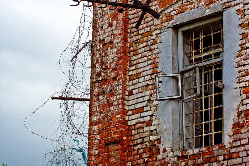 Fenêtre en cellule de prison avec des barres et barbelé dans une vieille prison en Sibérie, en Russie images stock