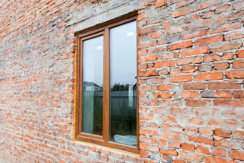 Fenêtre en plastique simple sur un mur avec les briques rouges fenêtre de nstall contre la façade de mur de briques photo stock