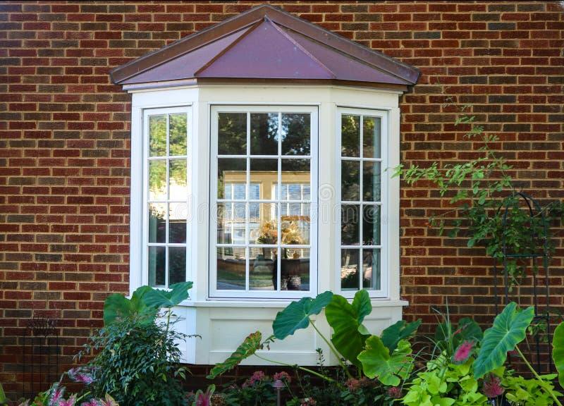 Fenêtre en saillie dans une maison de brique avec la réflexion des arbres et la vue des fenêtres et des fleurs intérieures et des photographie stock