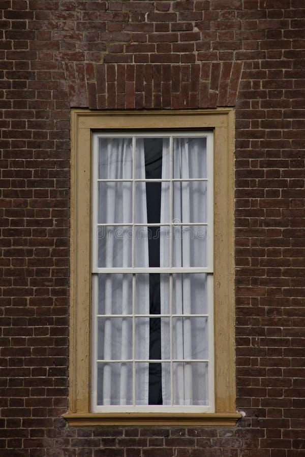 Fenêtre encadrée par jaune simple sur le mur de briques rouge. photographie stock