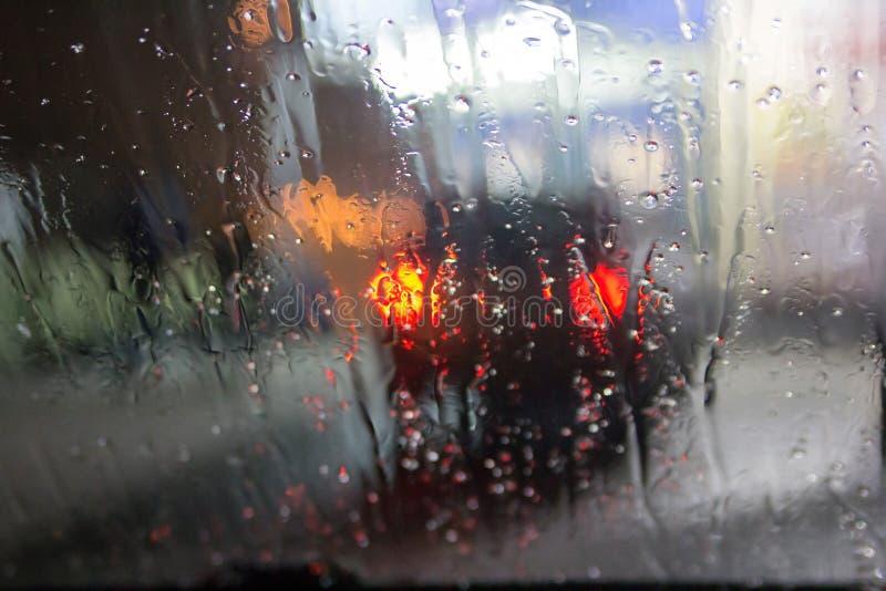 Fenêtre humide avec le fond de la vue de circulation urbaine de nuit images stock