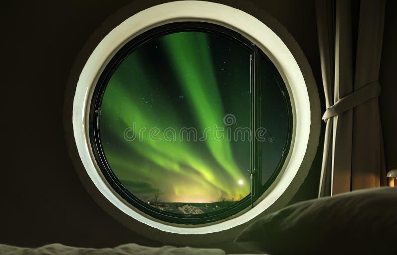 Fenêtre intérieure de cercle dans la chambre à coucher avec la belle vue d'Aurora Borealis de lumières du nord la nuit image libre de droits