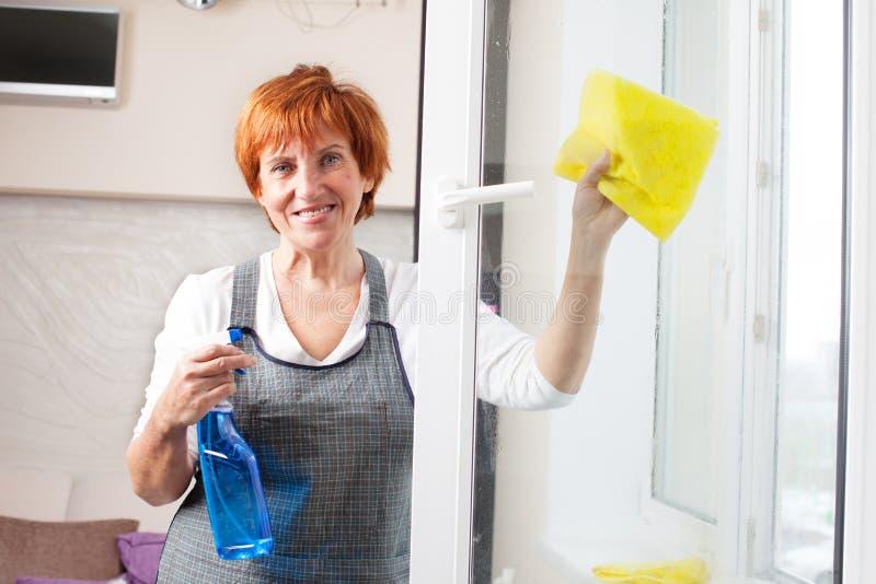 Fenêtre mûre de nettoyage de femme image stock