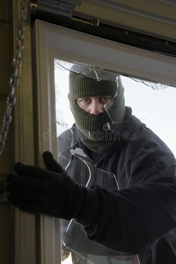 Fenêtre masquée de Breaking In Through de voleur images stock