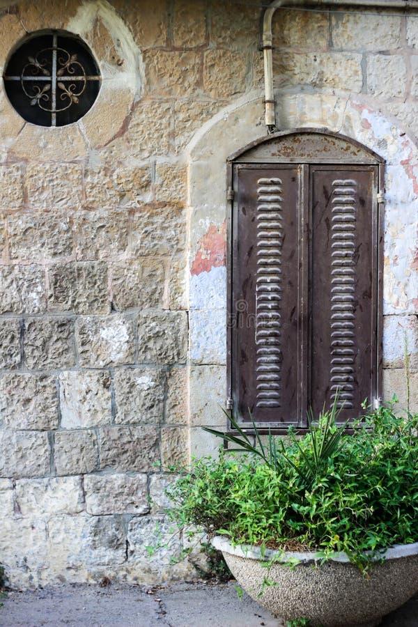 Fenêtre ronde avec le trellis à jour de fer travaillé et fenêtre avec des volets de fer images stock