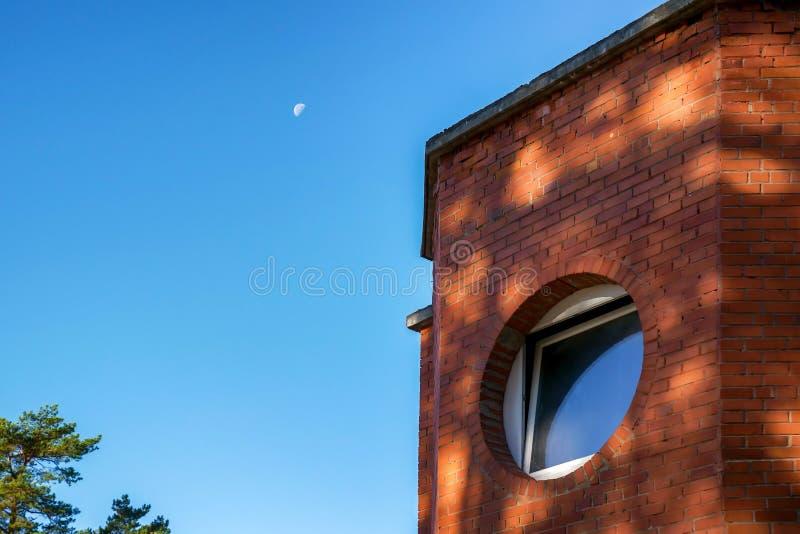 Fenêtre ronde de cercle sur le mur de briques rouge construisant au-dessus du ciel bleu clair avec la lune dans le matin photo stock