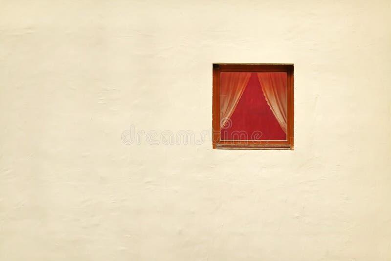 Fenêtre rouge simple avec des rideaux dans le mur blanchi photo stock