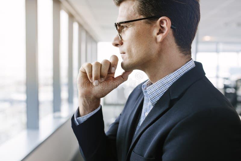 Fenêtre se tenante prêt et pensée d'homme d'affaires mûr photos stock