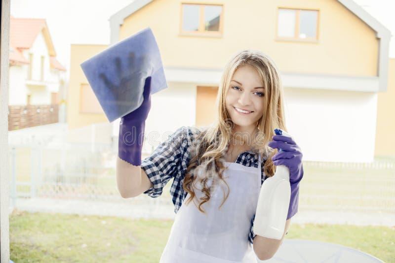 Fenêtres attrayantes de nettoyage de jeune femme dans la maison image libre de droits