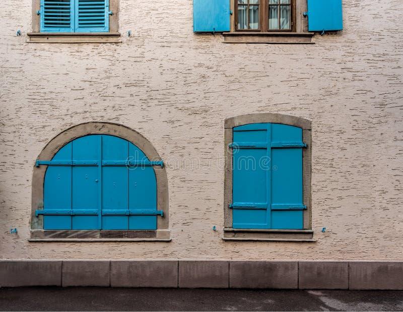 Fenêtres bleues sur les murs jaune pâle d'une petite ville images stock