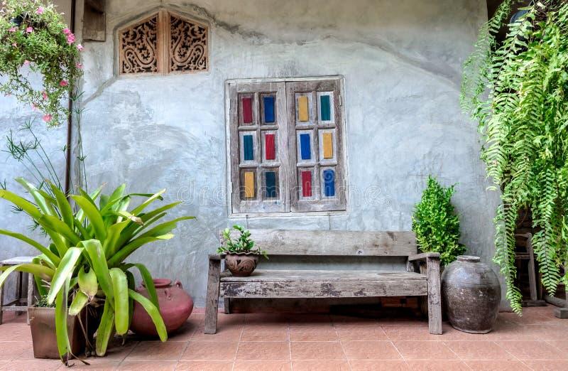 Fenêtres colorées de cru derrière la longue chaise en bois de cru photographie stock