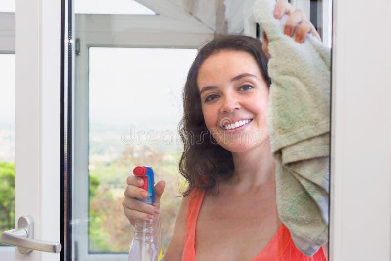 Fenêtres de lavage de jeune femme dans la maison image libre de droits