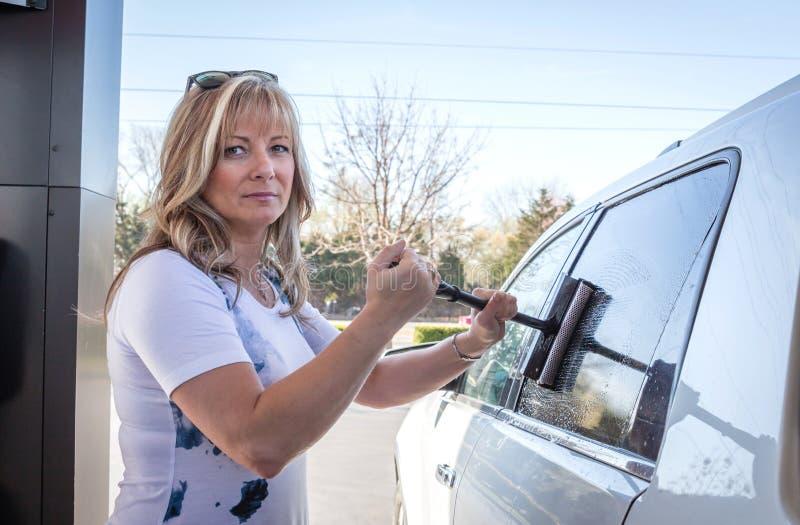 Fenêtres de voiture caucasiennes blondes de nettoyage de femme à la station service image stock