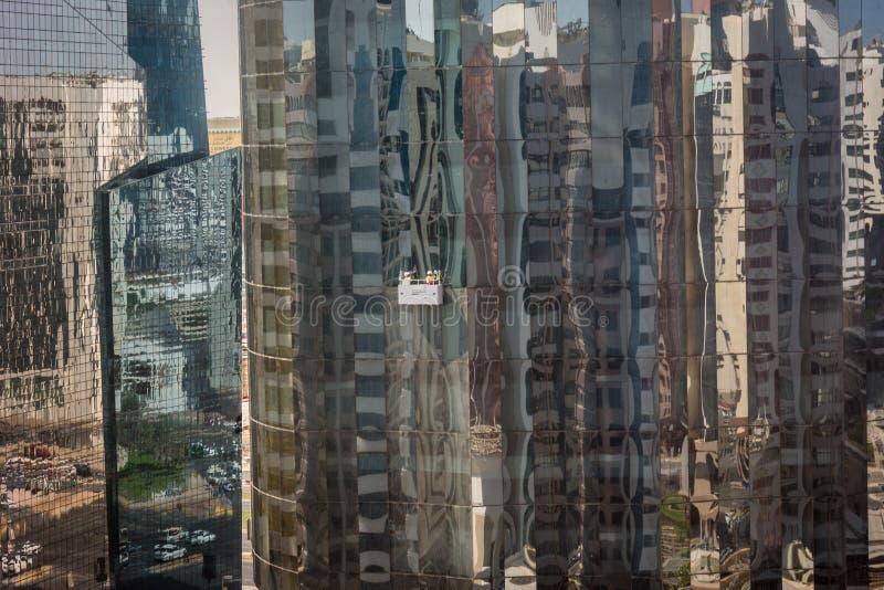 Fenêtres en verre de tour de nettoyage en ville d'Abu Dhabi photographie stock libre de droits