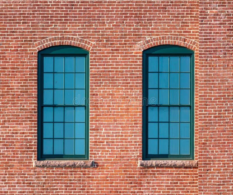 Fenêtres encadrées vertes dans un mur de briques images libres de droits