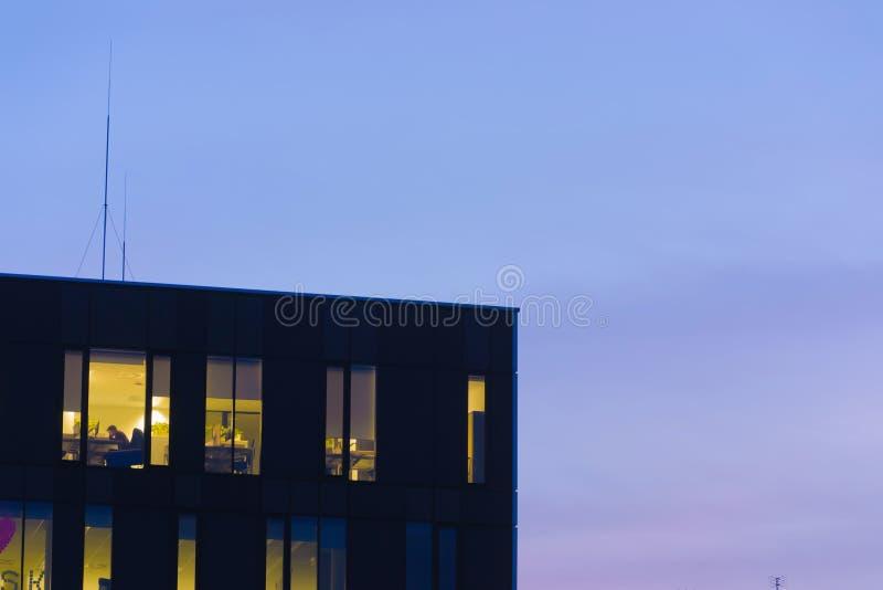 Fenêtres parfaites d'immeuble de bureaux au modèle de crépuscule beaucoup nuit semblable images stock