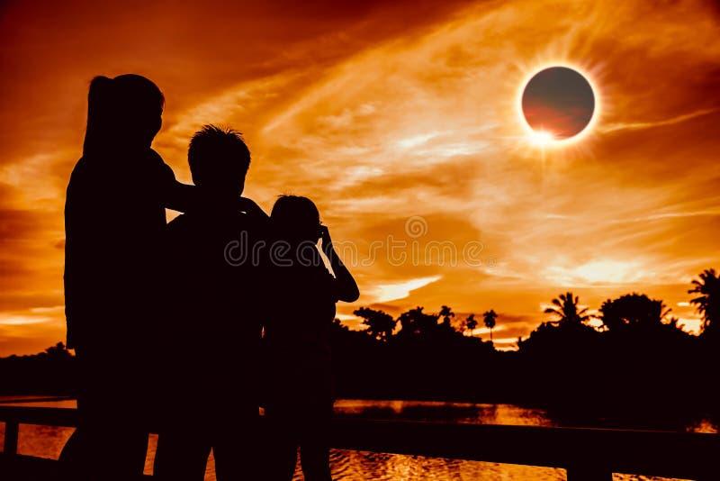 Fenómeno natural En eclipse solar total de mirada de tres personas imagen de archivo libre de regalías