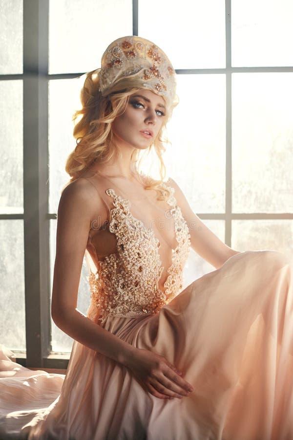 Fen med långt blont hår i ljus är på bakgrund av ett stort fönster, konstmodeflicka Härligt blont kvinnasammanträde arkivfoto