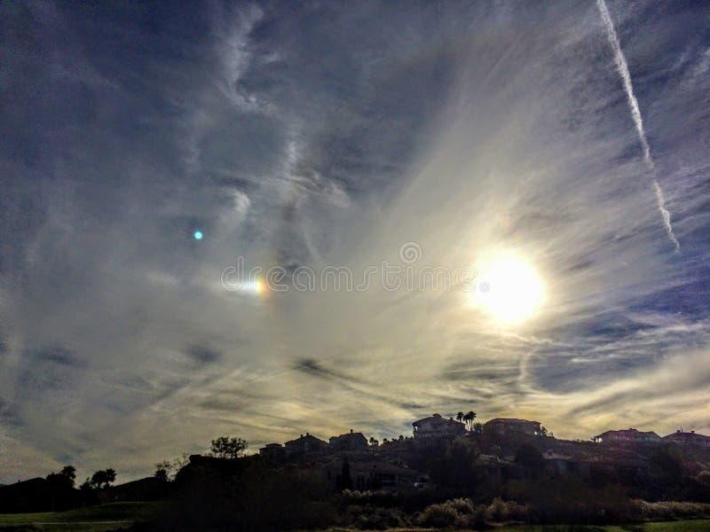 Fenômeno do cão de Sun perto do por do sol nas nuvens e no córrego de jato sobre St George Neighborhood foto de stock